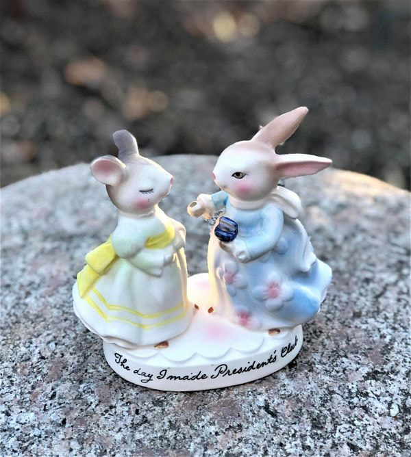 Bunny in blue dress presenting a pin or key to mouse in yellow dress